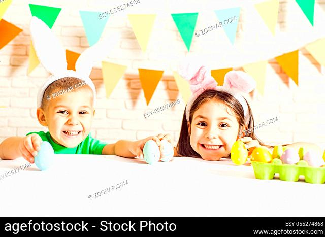 The kids with bunny ears are playing with Easter eggs at home. The little boy and girl during Easter morning at the table with Easter eggs