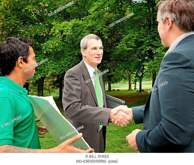 Businessmen shaking hands in park
