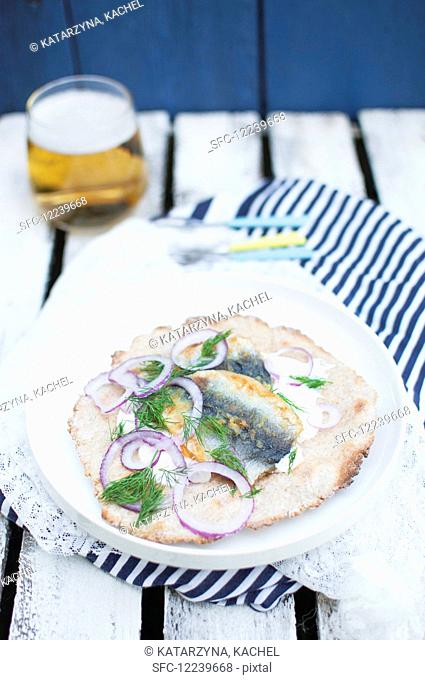 Fried herring with homemade crispbread, sour cream, red onion and fresh dill (Swedish street food)