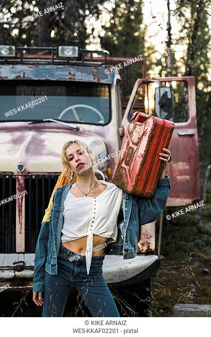 Young woman posing at a broken vintage truck, holding petrol can