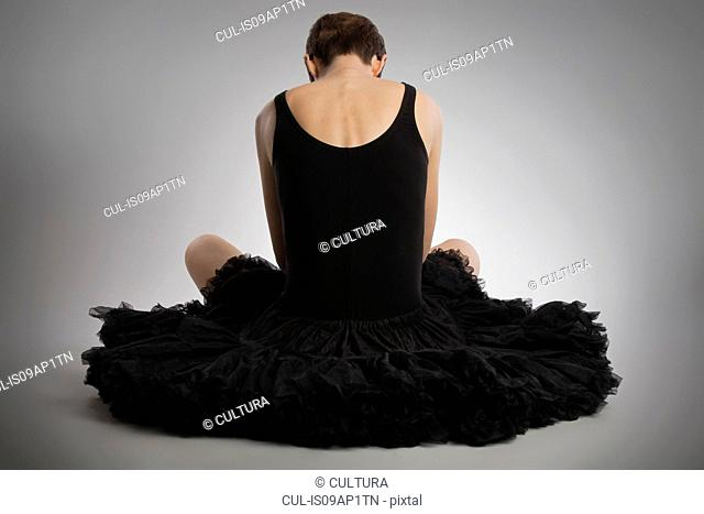 Rear view of woman sitting on floor wearing black tutu