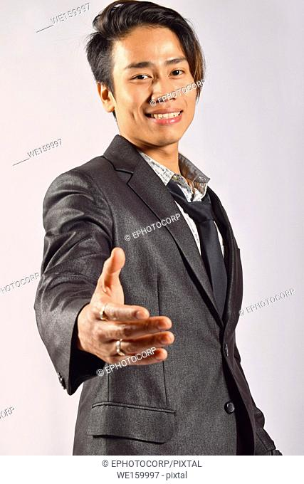 Indian male model extending a handshake towards camera, Pune, Maharashtra