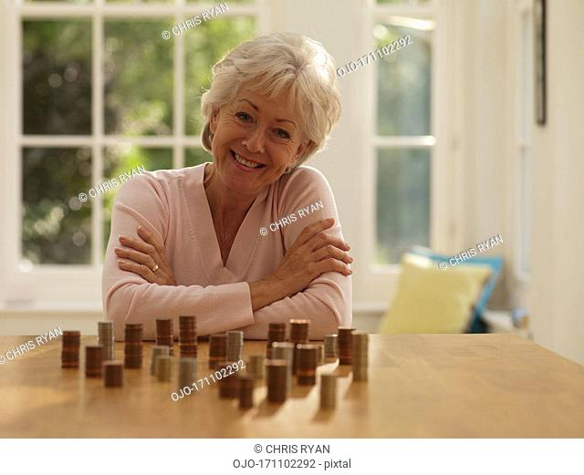 Smiling woman with coins stacks
