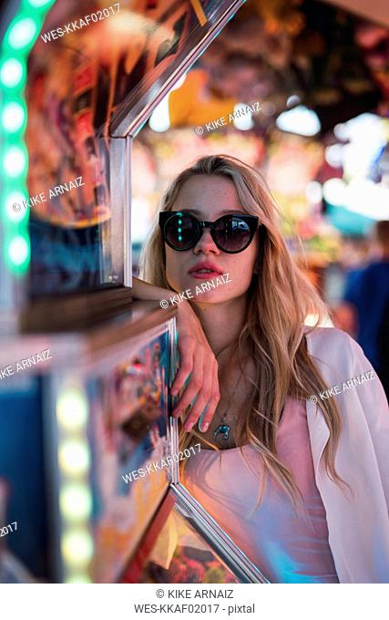 Portrait of young woman wearing sunglasses on a funfair
