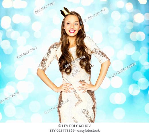 people, holidays and celebration concept - happy young woman or teen girl in party dress and princess crown over blue lights background
