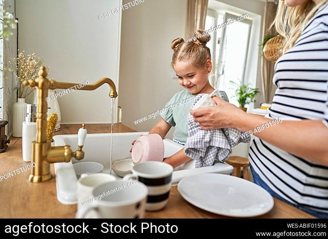 Smiling daughter washing crockery in sink with mother at home