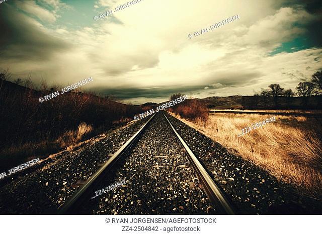 Steel railways train tracks run asymmetrically parallel into a vanishing viewpoint. Vintage freight lines and logistics, Woodbury, Tasmania, Australia