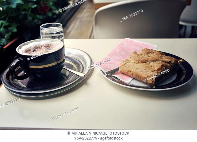 Glass of water, teaspoon, coffee cup on a plate and Apple strudel, close up, Vienna, Austria