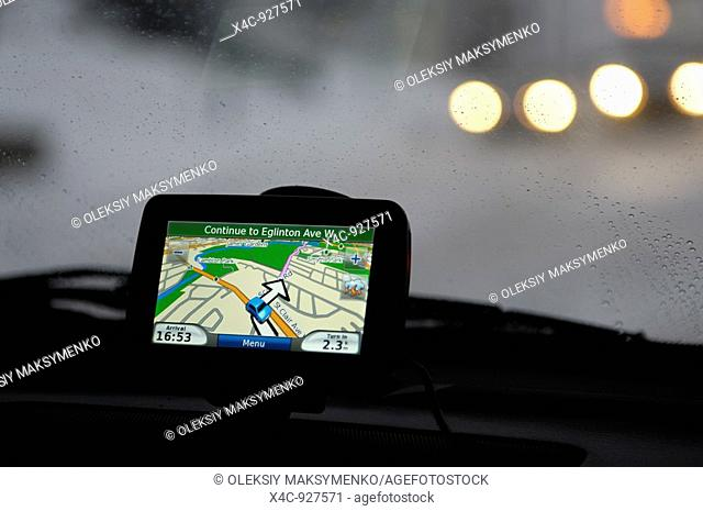 GPS navigational device on a dashboard of a car in winter night