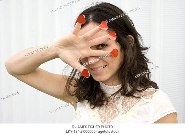 Portrait of woman with heart shapes on fingers