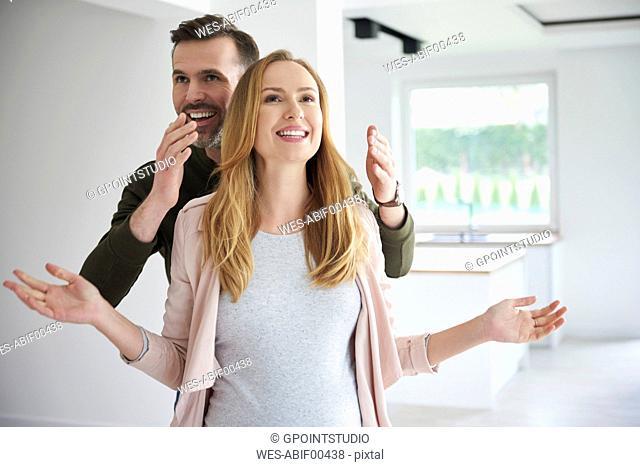Man surprising woman in empty flat