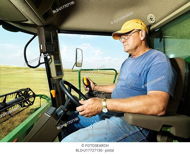 Farmer driving combine and harvesting crop