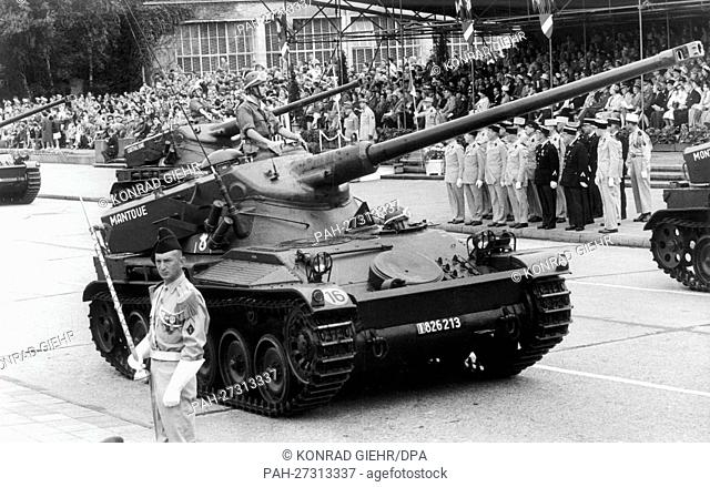 Tanks drive past the spectators and the honorary tribune during the parade on the occasion of the French national day on the 14th of July in 1961 in the...
