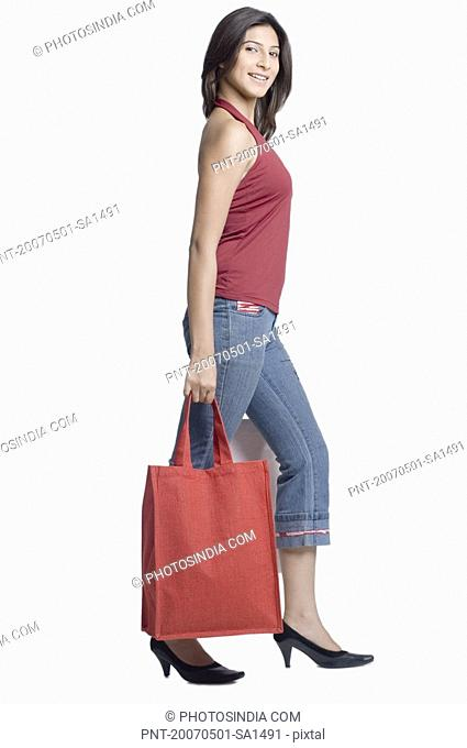Portrait of a young woman holding a shopping bag and smiling