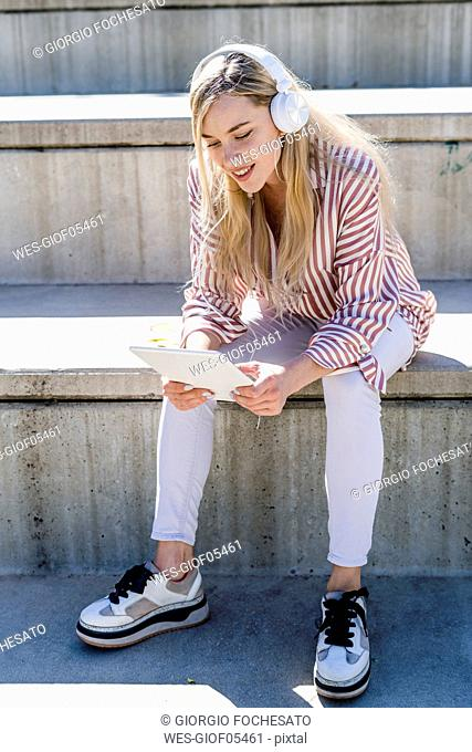 Portrait of blond young woman sitting on stairs outdoors using digital tablet and headphones