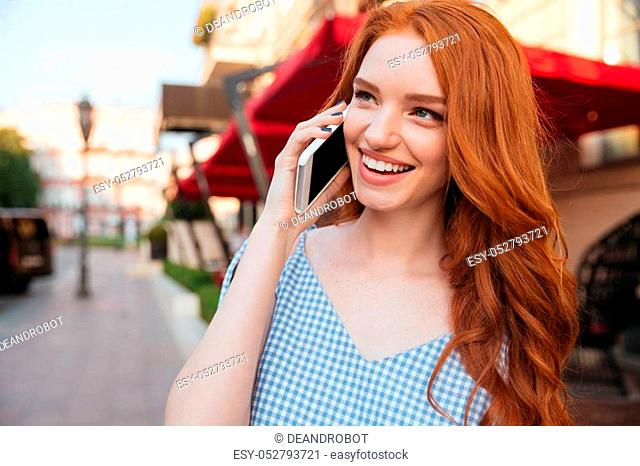 Close up of smiling attractive girl with long hair talking on mobile phone while standing outdoors on a city street