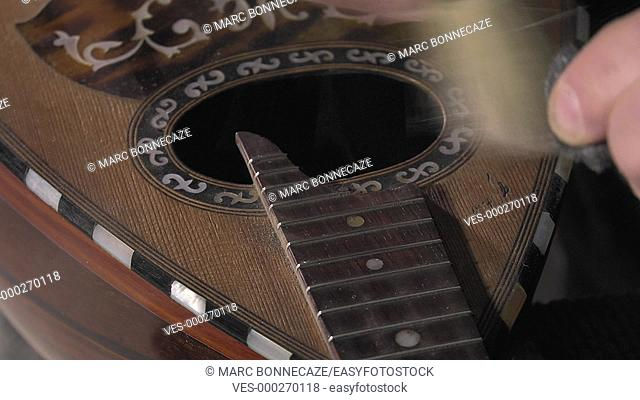 cleaning button and the frets of an old mandolin