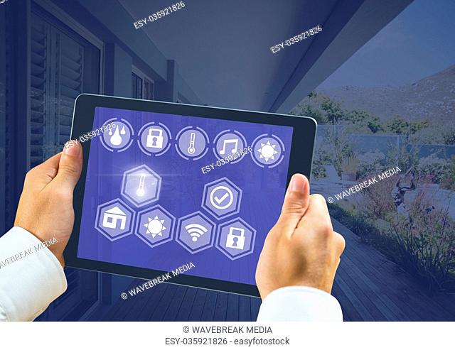 Hand holding tablet with smart home interface at home