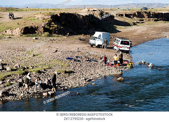 Cleaning cars and clothes in a river near Puno, Peru. Peruvian altiplano landscape seen from inside the Andean Explorer train Orient Express which runs between...