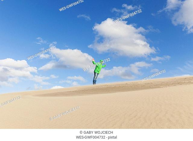 Man standing on sand dune in storm
