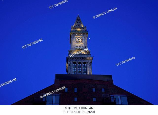Illuminated clock tower at dawn