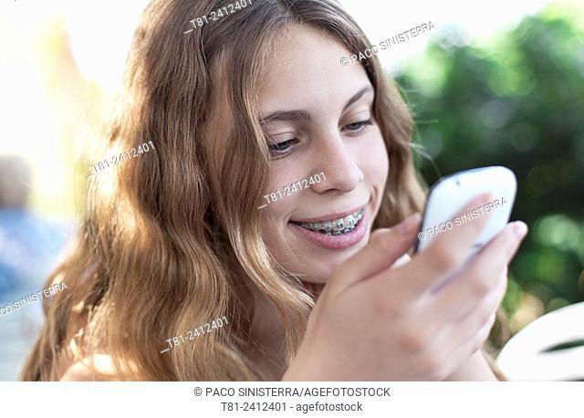 girl, mobil phone looking agenda, the garden, Calpe, Spain