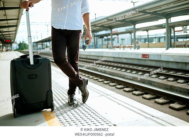 Man with suitcase waiting at station platform