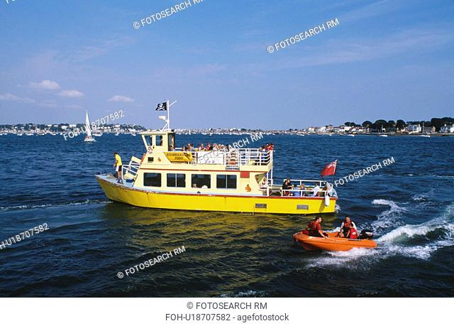 Small orange boat beside yellow passenger boat on the sea in Poole Harbour in Dorset
