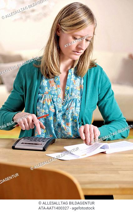 Woman with pocket calculator and statements of account