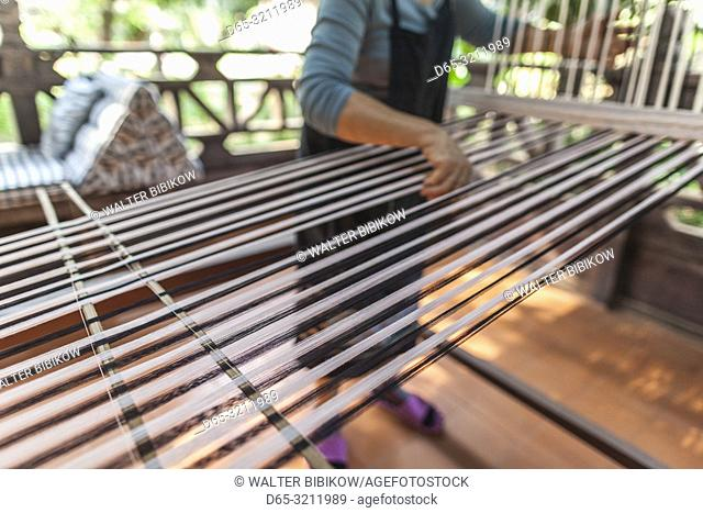 Laos, Vientiane, Lao Textile Museum, weaver working traditional Lao loom, NR