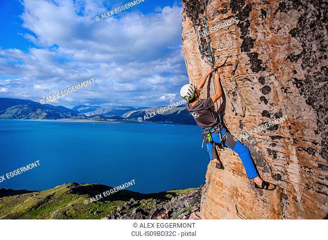 Young male climber climbing sandstone rockface, Narsaq, Vestgronland, South Greenland