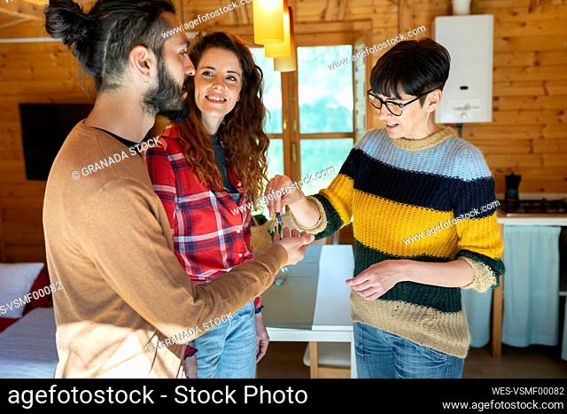 Host welcoming young couple in a cabin in the countryside handing over house key