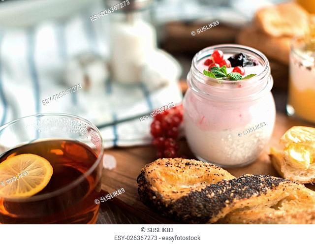 cream mousse with a mint and red currant and buns and hot tea with lemon on a wooden table