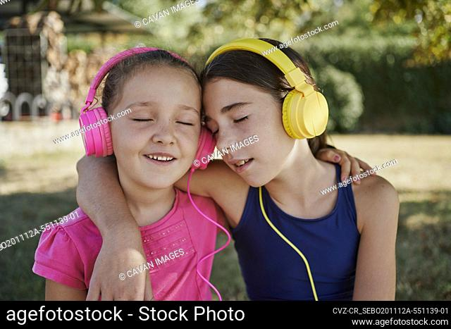 Little girls listening to music and close their eyes with yellow and pink headphones in a garden. relax concept