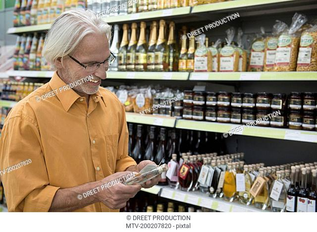Customer reading label on a schnapps bottle in supermarket, Augsburg, Bavaria, Germany