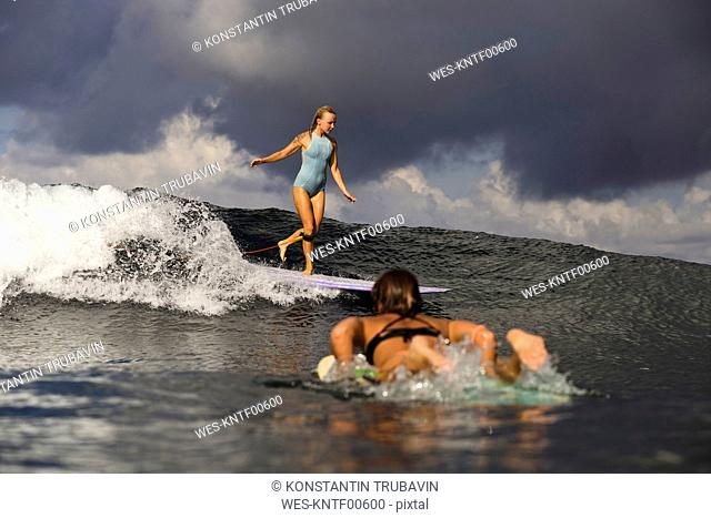 Indonesia, Bali, two women surfing
