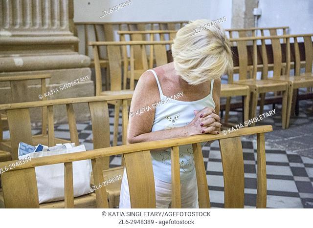 Caucasian blond woman on her knees praying in a church in france