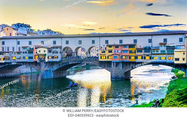 Evening Sunset Dinner Party Arno River Ponte Vecchio Florence Tuscany Italy. Bridge originally built in Roman times, rebuilt in 1345