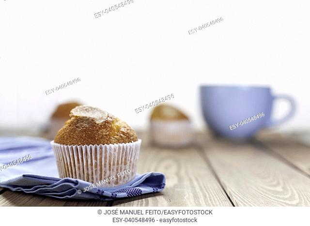 muffin cupcake on blue napkin and blue cup on wood table and white background