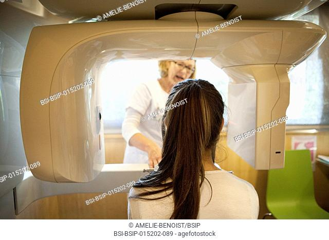 Reportage in a radiology centre in Haute-Savoie, France. A technician positions a young patient for a panoramic dental x-ray