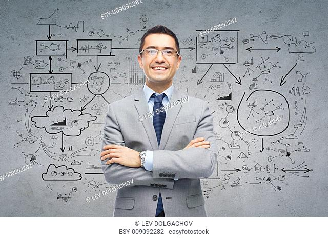business, people, development and planning concept - happy smiling businessman in eyeglasses and suit over gray concrete with scheme background