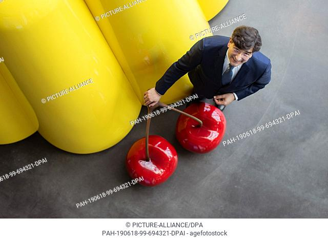 18 June 2019, North Rhine-Westphalia, Bielefeld: Albert Christmann, personally liable partner of Dr. August Oetker KG, stands next to an oversized pudding at...
