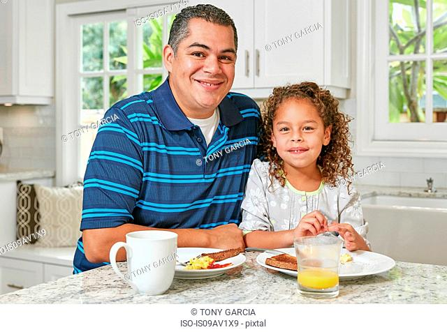 Father and daughter side by side at kitchen counter eating breakfast, looking at camera smiling
