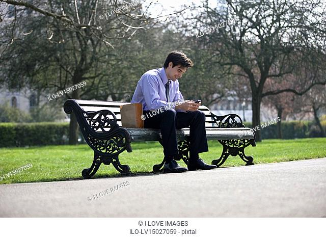 A businessman sitting on a bench, using his mobile phone