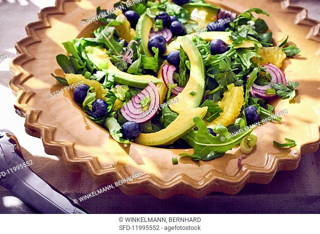 Avocado salad with rocket, onion, blueberries and oranges