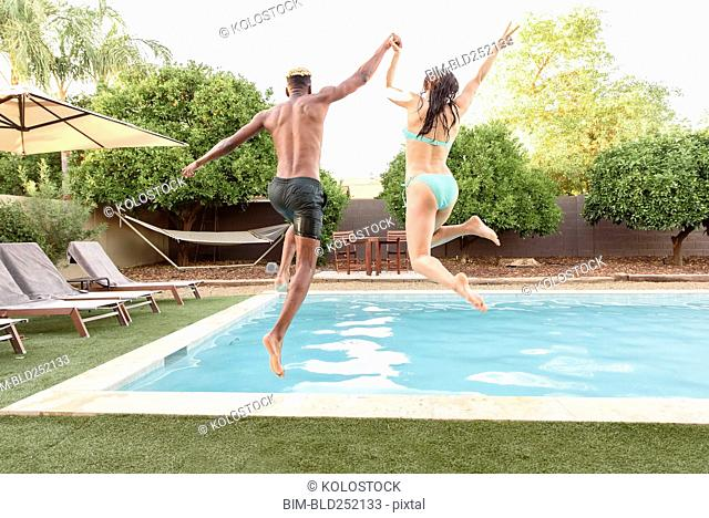 Couple holding hands jumping into swimming pool