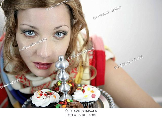 Portrait of a beautiful young woman with cupcakes in foreground