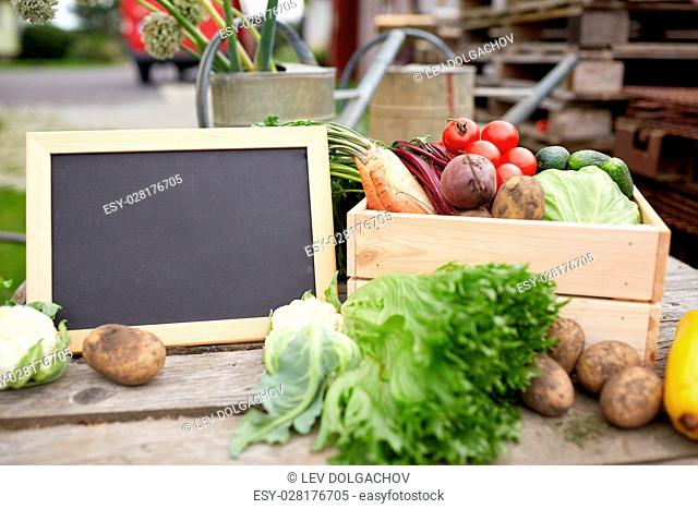 harvest, food and agriculture concept - close up of vegetables with chalkboard on farm