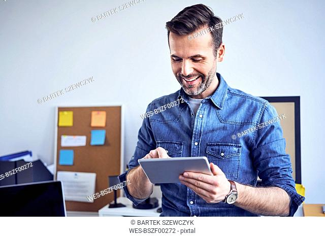 Smilig man using tablet in office