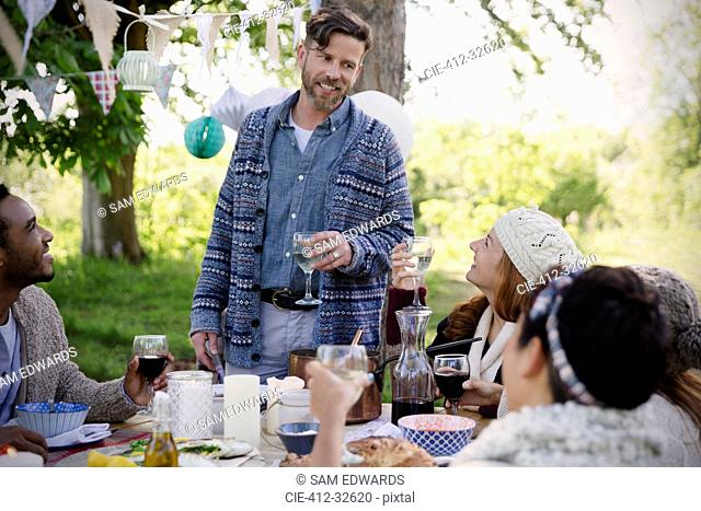 Man toasting friends at garden party table